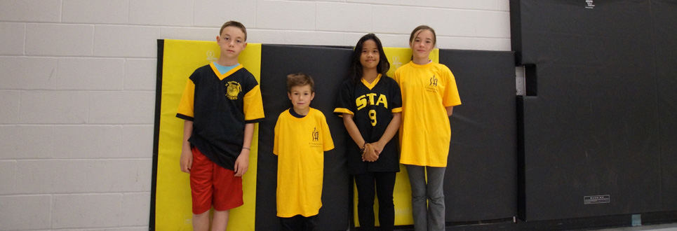 St. Thomas Aquinas Catholic School athletes wearing yellow and black sports uniforms.