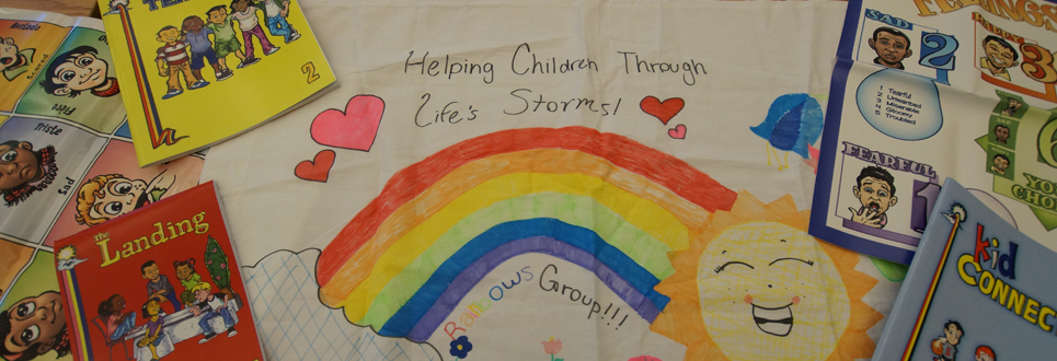 "Poster with a rainbow and hearts with, ""Helping Children Through LIfe's Storms"" written above the rainbow. Various testing booklets and mental health posters are placed along the sides of the poster."