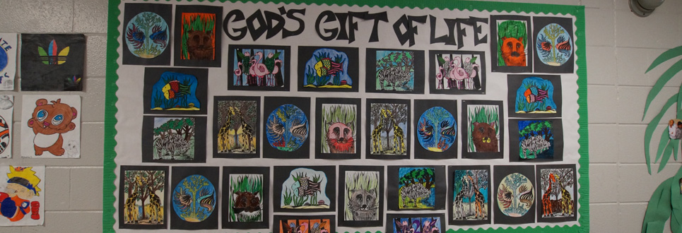 "Bulletin board filled with student artwork of various animals with the title, ""God's Gift of Life"" at the top."